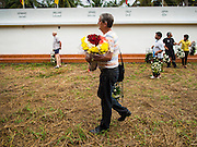 26 DECEMBER 2014 - MAE KHAO, PHUKET, THAILAND: PAUL BILNEY, originally from Australia and now living in Phuket, carries roses to the Tsunami Memorial Wall in Mae Khao, Phuket. Bilney said he came to Phuket as a volunteer after the tsunami and moved to Phuket after that. The wall is located at the site that was used as the main morgue for people killed in the tsunami and hosts an annual memorial service. Nearly 5400 people died on Thailand's Andaman during the 2004 Indian Ocean Tsunami that was spawned by an undersea earthquake off the Indonesian coast on Dec 26, 2004. In Thailand, many of the dead were tourists from Europe. More than 250,000 people were killed throughout the region, from Thailand to Kenya. There are memorial services across the Thai Andaman coast this weekend.    PHOTO BY JACK KURTZ