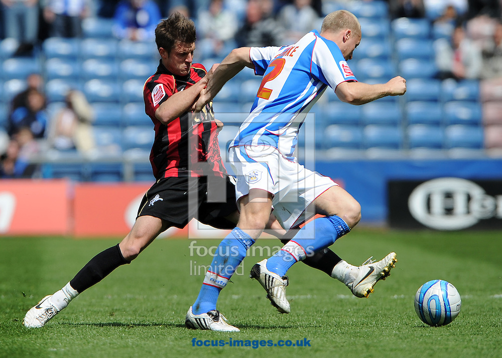 Huddersfield- Saturday May 15th, 2010: Peter Clarke of Huddersfield Town skips past the challenge of Millwall's Scott Barron during the Coca-Cola League 1 Playoff Semi Final 1st leg match at The Galpharm Stadium, Huddersfield. (Pic by Andrew Stunell/Focus Images)..