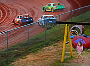 """Hailey McCurry, 9, of Lancaster, sits in a swing as race cars make their way to turn one during a race in August. The play area above the track is a popular destination for children of all ages. """"Dirt Track"""""""