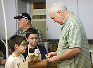Sam Brewster (from left), 10, of Cedar Rapids and Brandon Box, 11, of Newhall listen to some instructions from Cedar Valley Woodcarvers President John Marion during a meeting of the Cedar Valley Woodcarvers in Midway on Saturday, May 25, 2013.