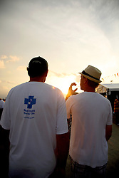 05 May 2012. New Orleans, Louisiana,  USA. .New Orleans Jazz and Heritage Festival. .Friends leaving discuss the festival. One wearing a New Orleans Musician's Clinic t-shirt - an organisation supported by Jazzfest, responsible for keeping the beat alive in schools and communities throughout the city..Photo; Charlie Varley.