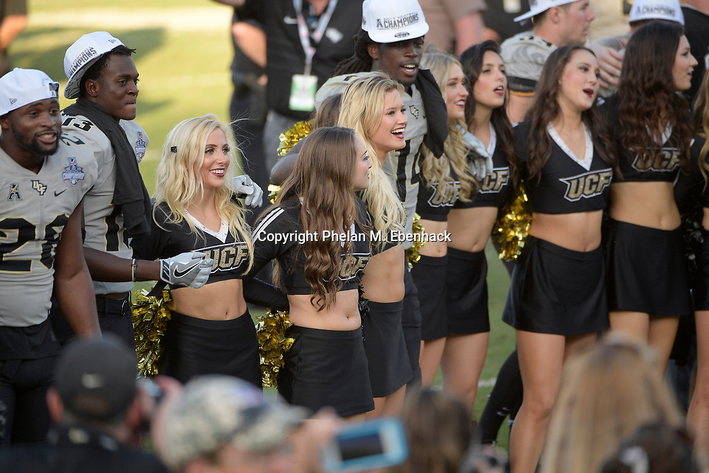 Central Florida cheerleaders celebrate with players on the field after the American Athletic Conference championship NCAA college football game against Memphis Saturday, Dec. 2, 2017, in Orlando, Fla. Central Florida won 62-55. (Photo by Phelan M. Ebenhack)