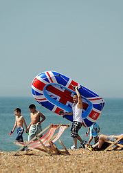 © licensed to London News Pictures. BRIGHTON  UK. 21/04/11.People flock to Brighton Beach today to catch the sunshine before the start of the Easter Bank Holiday in Britain. Temperatures are set to continue to rise over the weekend. Photo credit should read Stephen Simpson/LNP