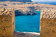 A view through a wall at the Acropolis to Lindos Bay, Lindos, Rhodes, Dodecanese Islands, Greece