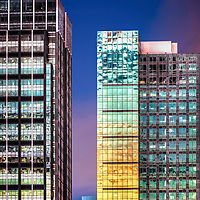 Downtown Seattle's glass-curtain buildings captured at twilight against a clear sky.