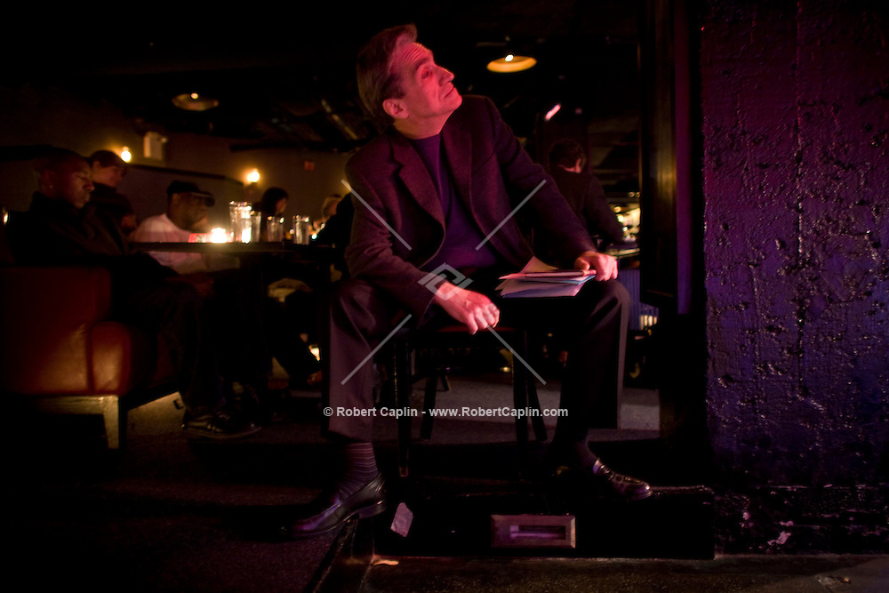 Former laureate, Robert Pinsky, right, sits off-stage while listening to jazz between readings of some poetry during a collaboration with jazz musicians at the Jazz Standard in New York, U.S. 1/8/08.