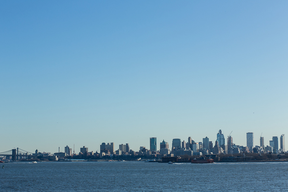 Liberty Island, NY - 9 January 2020. Dwontown Brooklyn, and the eastern end of the Brooklyn Bridge, seen from Liberty Island.