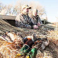 duck hunters in blind with ducks