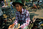 BURMA (Myanmar) - Mandalay. A cycle rickshaw driver takes a break from peddling and reads from his passenger seat.