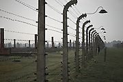 View of Auschwitz 11 Birkenau. Electrified fences and the chimneys that remain of the wooden barracks.Poland.