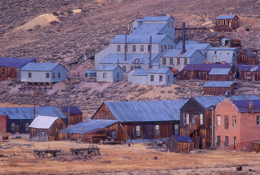 Bodie ghost town at dusk with old Standard Stamp Mill buildings on hillside; Bodie State Historical Park, California.