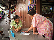 10 SEPTEMBER 2015 - BANGKOK, THAILAND: Women on Thetsaban Sai 1 Road, a pedestrian footpath next to Wat Kalayanamit. The homes on the path are scheduled to be demolished in the next week. Authorities started to destroy 54 homes in front of Wat Kalayanamit, a historic Buddhist temple on the Chao Phraya River in the Thonburi section of Bangkok. Government officials, protected by police, seized the house of Chaiyasit Kittiwanitchapant, a Kanlayanamit community leader, who has led protests against the temple's abbot for trying to evict community members whose houses are located around the temple. Work crews went into Chaiyasit's home and took it apart piece by piece. The abbot of the temple said he was evicting the residents, who have lived on the temple grounds for generations, because their homes are unsafe and because he wants to improve the temple grounds. The evictions are a part of a Bangkok trend, especially along the Chao Phraya River and BTS light rail lines, of low income people being evicted from their long time homes to make way for urban renewal.     PHOTO BY JACK KURTZ