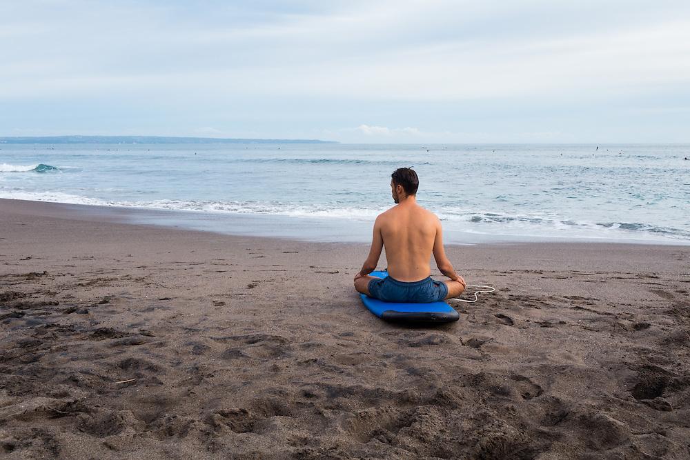 A man sits on his surf board at Batubolong beach in Canggu.