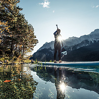 Junge Frau paddelt am SUP Board in der Morgensonne über den Eibsee, Blick zur Zugspitze, Garmisch-Partenkirchen, Bayern, Deutschland. * Young woman stand-up-paddling on Lake Eibsee in the morning light, overlooking the Zugspitze Mountain, Garmisch-Partenkirchen, Bavaria, Germany.