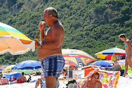Portuguese Summer. A man eat a sandwich and drink a beer at Portinho da Arrábida beach.