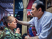 "25 MAY 2015 - BANGKOK, THAILAND: KAN (left) who has a Sak Yant tattoo, is blessed by AJARN NENG ONNUT (also known as Khun Pean) in his tattoo parlor in Bangkok. Sak Yant (Thai for ""tattoos of mystical drawings"" sak=tattoo, yantra=mystical drawing) tattoos are popular throughout Thailand, Cambodia, Laos and Myanmar. The tattoos are believed to impart magical powers to the people who have them. People get the tattoos to address specific needs. For example, a business person would get a tattoo to make his business successful, and a soldier would get a tattoo to help him in battle. The tattoos are blessed by monks or people who have magical powers. Ajarn Neng, a revered tattoo master in Bangkok, uses stainless steel needles to tattoo, other tattoo masters use bamboo needles. The tattoos are growing in popularity with tourists, but Thai religious leaders try to discourage tattoo masters from giving tourists tattoos for ornamental reasons.       PHOTO BY JACK KURTZ"