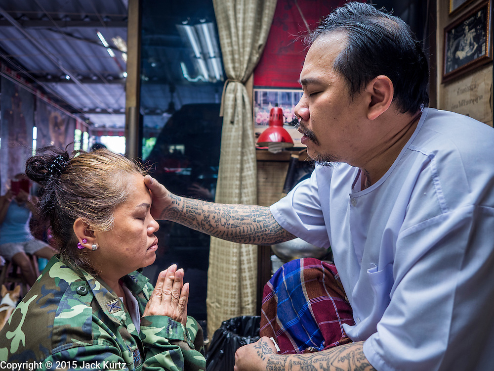 """25 MAY 2015 - BANGKOK, THAILAND: KAN (left) who has a Sak Yant tattoo, is blessed by AJARN NENG ONNUT (also known as Khun Pean) in his tattoo parlor in Bangkok. Sak Yant (Thai for """"tattoos of mystical drawings"""" sak=tattoo, yantra=mystical drawing) tattoos are popular throughout Thailand, Cambodia, Laos and Myanmar. The tattoos are believed to impart magical powers to the people who have them. People get the tattoos to address specific needs. For example, a business person would get a tattoo to make his business successful, and a soldier would get a tattoo to help him in battle. The tattoos are blessed by monks or people who have magical powers. Ajarn Neng, a revered tattoo master in Bangkok, uses stainless steel needles to tattoo, other tattoo masters use bamboo needles. The tattoos are growing in popularity with tourists, but Thai religious leaders try to discourage tattoo masters from giving tourists tattoos for ornamental reasons.       PHOTO BY JACK KURTZ"""