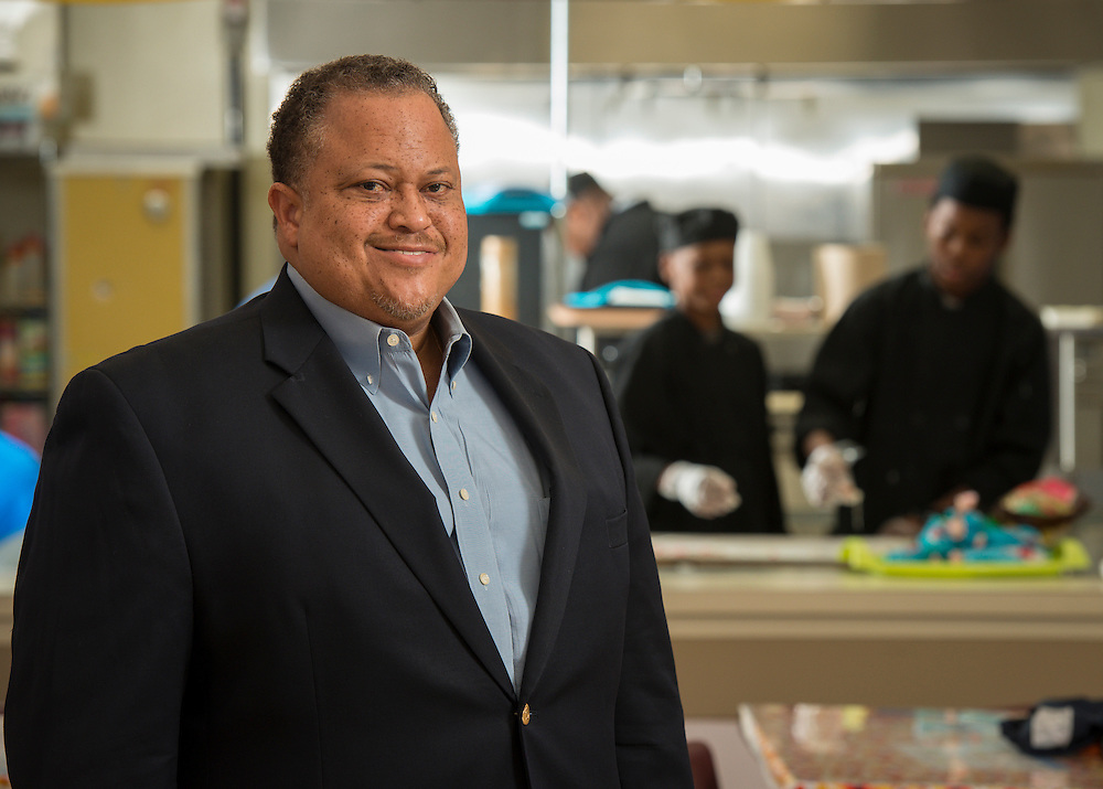 Principal Raymond Glass poses for a photograph in the culinary arts class at Harper School, December 18, 2013.