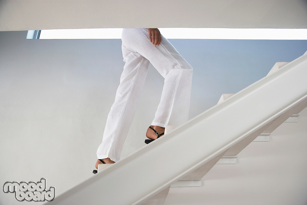 Woman walking up staircase indoors low section