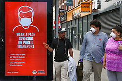© Licensed to London News Pictures. 22/05/2020. London, UK. People wearing face coverings in north London look at a 'WEAR A FACE COVERING ON PUBLIC TRANSPORT'  digital poster, which is a part of the London for Transport's public information campaign as the lockdown is eased. Photo credit: Dinendra Haria/LNP
