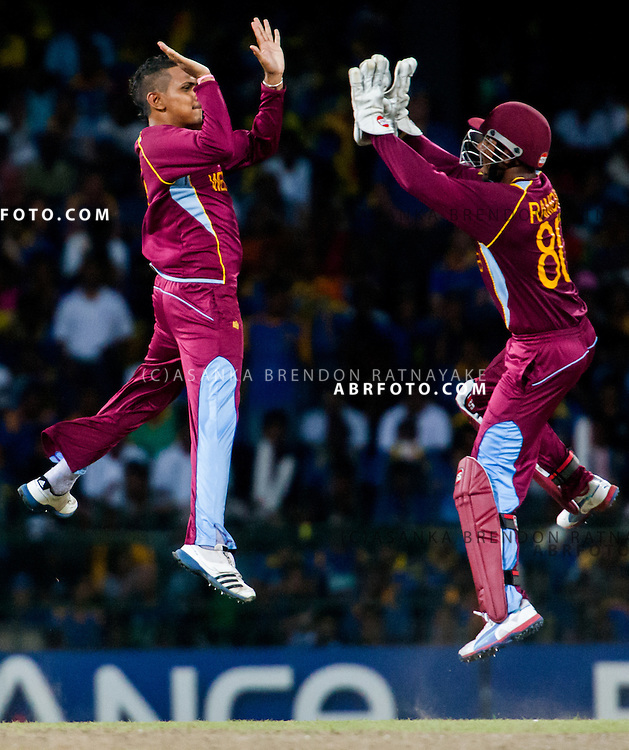 West Indians Sunil Narine and Denesh Ramdin jump in celebration after getting a wicket during the World T20 Cricket Mens Final match between Sri Lanka Vs West Indies at the R Premadasa International Cricket Stadium, Colombo. Photo credit : Asanka Brendon Ratnayake