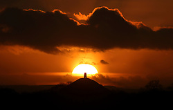 © Licensed to London News Pictures. 24/12/2015. Glastonbury, UK. The sun setting behind Glastonbury Tor in Somerset on Christmas Eve 2015. . Photo credit: Jason Bryant/LNP