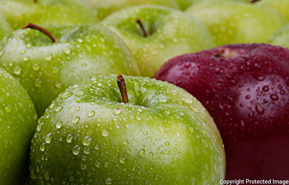 Green and red apples sprinkled with water