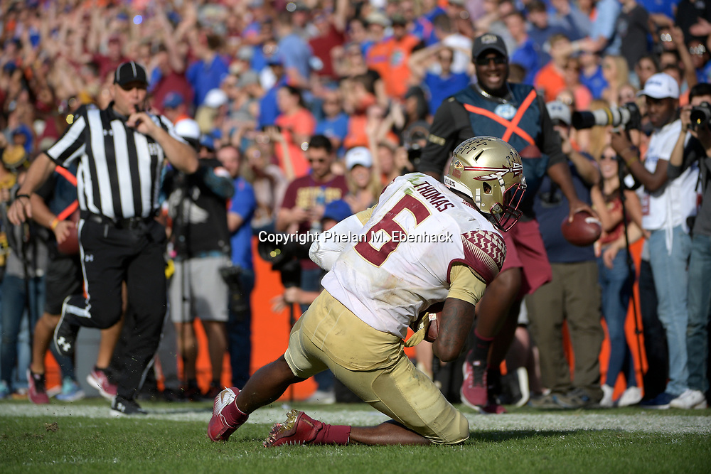 Florida State linebacker Matthew Thomas (6) falls short of the goal line after intercepting a pass and running it back during the second half of an NCAA college football game against Florida Saturday, Nov. 25, 2017, in Gainesville, Fla. FSU won 38-22. (Photo by Phelan M. Ebenhack)
