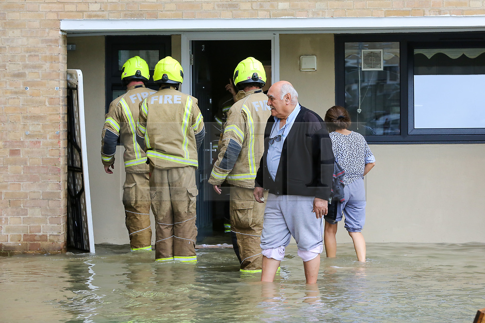 © Licensed to London News Pictures. 08/10/2019. London, UK. Firemen outside a ground floor flat in Theobalds Court as the residents stand in water following a burst water main on Brownswood Road in Finsbury Park, north London. Photo credit: Dinendra Haria/LNP