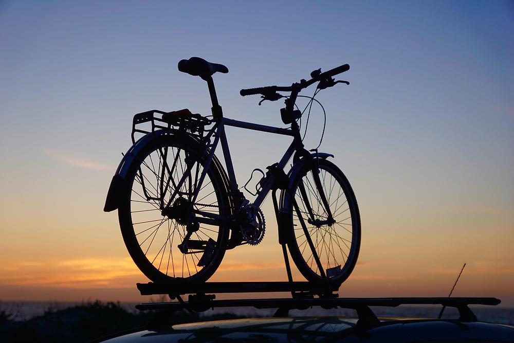 Bicycle atop car and sunset, Asilomar Beach, Pacific Grove, California