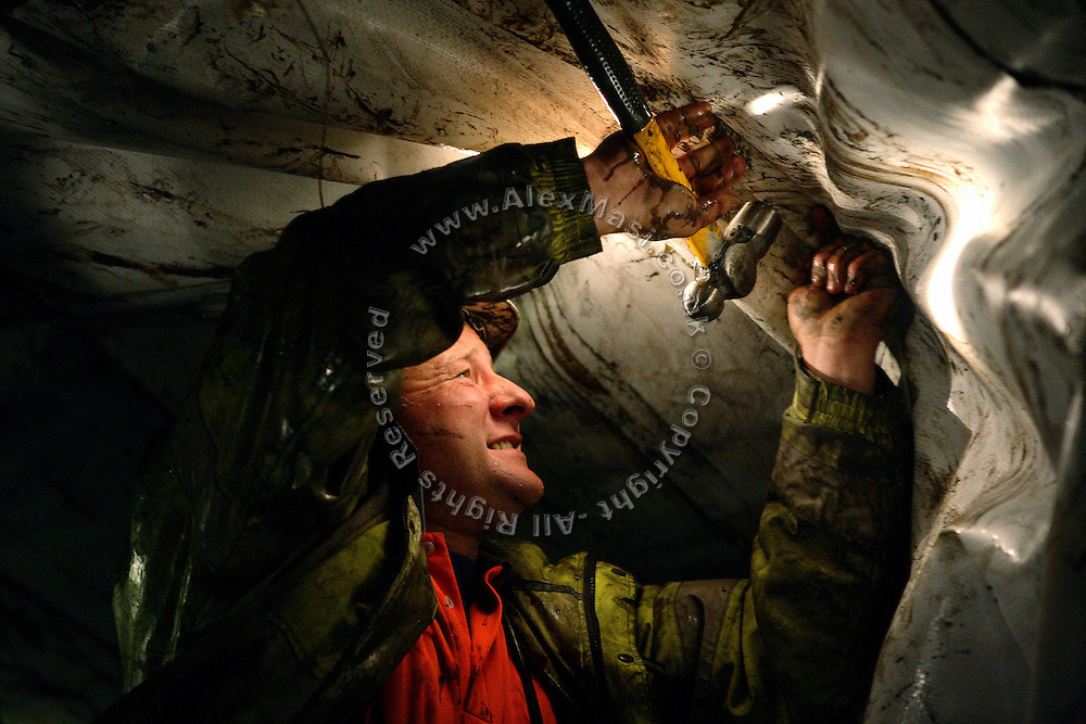 A miner is having troubles while attempting to fix a water leakage inside Unity Mine, on Monday, June 18, 2007, in Cwmgwrach, Vale of Neath, South Wales. The time is ripe again for an unexpected revival of the coal industry in the Vale of Neath due to the increasing prize and diminishing reserves of oil and gas, the uncertainties of renewable energy sources, and the technological advancement in producing energy from coal while limiting emissions of pollutants, has created the basis for valuable investment opportunities and a possible alternative to the latest energy crisis. Unity Mine, in particular, has started a pioneering effort to revive the coal industry in the area, reopening after more than 8 years with the intent of exploiting the large resources still buried underground. Coal could be then answer to both, access to cheaper and paradoxically greener energy and a better and safer choice than nuclear energy as a major supply for the decades to come. It is estimated that coal reserves in Wales amount to over 250 million tonnes, or the equivalent of at least 50 years of energy supply, while the worldwide total coal could last for over 200 years as a viable resource compared to only a few decades of oil and natural gas.