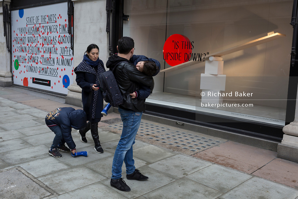 An Asian family struggle with a blue boot outside a window display that is part of a design theme called 'State of the Arts', at the Selfridges department store on Oxford Street, on 4th March 2019, in London England. State of the Arts is a gallery of works by nine crtically-acclaimed artists in Selfridges windows to celebrate the power of public art. Each of the artists are involved in creating a site-specific artwork at one of the new Elizabeth line stations as part of the Crossrail Art Programme.