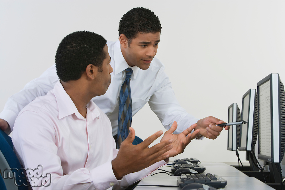 Two business men discussing in front of computer