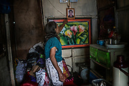 Remy Fernandez, 84 years old, points to a portrait of her late son, Constantino de Juan, who was a victim of an extrajudicial killing by masked assassins in this simple cinder block house built beside a massive mountain of garbage in Payatas, Metro Manila.<br /> <br /> She is raising seven grandchildren because after, Constantino, a methampetamine user, was killed by masked men and the mother, who is in prison due to a drug arrest could not raise them.   Metro Manila, Philippines