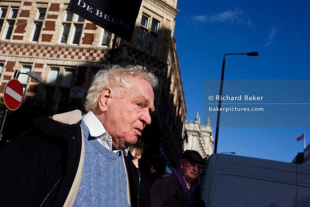 Elderly man walks through London street below No Entry sign.