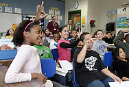 Thelma Outlaw, left, and other members of a fifth-grade class at Middletown's Maple Hill Elementary School wave to students from West Africa  after talking to them on Tuesday, Jan 12, 2010. The students used to computer program Skype to communicate, and the African students' images were projected onto the whiteboard in front of the classroom.