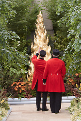 © licensed to London News Pictures. LONDON, UK  23/05/2011. Two Chelsea pensioners look at a £70,000, 11ft 6in (3.5m) high sculpture of a cypress tree covered in 23.5 carat gold at the 2011 RHS Chelsea Flower Show. The show held each year in the grounds of the Royal Chelsea Hospital and organised by the Royal Horticultural society opens to the general public tomorrow and is already sold out. Please see special instructions for usage rates. Photo credit should read CLIFF HIDE/LNP