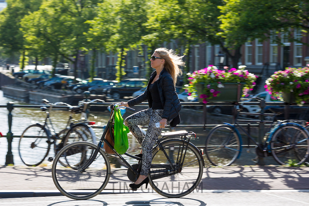Young woman wearing high heels shoes, carrying iPhone cycling out for the evening across bridge in Amsterdam, Holland