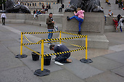 Tourists and a stone mason chips away at a cavity in damaged pavement, surrounded by hazzard tape in Trafalgar Square, central London.