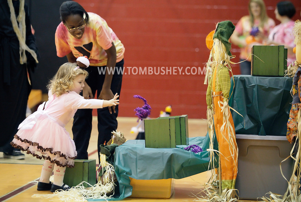 Middletown, New York - A volunteer watches a young girl in a costume plays a game in the gymnasium during the Middletown YMCA Family Fall Festival on Oct. 29, 2011. ©Tom Bushey / The Image Works