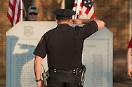 Goshen, New York - A police officer salutes after placing a flower in front of the monument during the Orange County Law Enforcement Officer Memorial Service on May 8, 2015, at the entrance of the Orange County Courthouse. The memorial service honors the memory of the members of the Orange County law enforcement community that died in the line of duty. The service also pays tribute the families and loved ones left behind for their courage, dignity and perseverance.