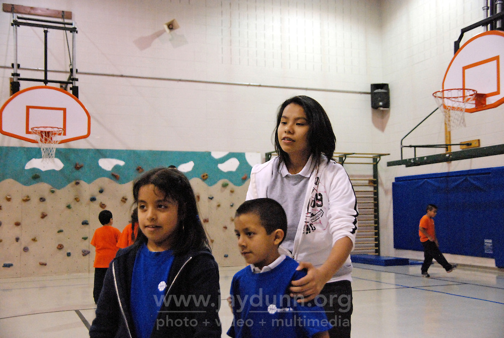 "USA, Chicago, IL, December 16, 2009.  Volunteer Rosalie Navarette has worked with the program five years. Founded ten years ago by Rob and Amy Castaneda, ""Beyond the Ball"" is a non-profit organization dedicated to giving kids and parents a healthy place to play together, whether it be in an after-school program or during an summer series of playground days, like last year's wildly successful ""Project Play."" The predominantly working-class neighborhoods of Little Village and North Lawndale have no park, and little public space for families that is safe from the gang violence endemic to large US cities. Beyond the Ball's approach is personal, and takes a long-term view - both Rob and Amy are neighborhood residents, and have experienced first-hand the anger of gang members. The group arranges for school facilities to be open late, such as this gym at Josefa Ortiz de Dominguez Elementary, and welcomes student volunteers who also get credit from Chicago Public Schools for doing community service. Many of the teenagers working with ""Beyond the Ball"" are comfortable as mentors, because they've been in the program before. It is easy to see the pride they take in teaching and taking responsibility for the younger kids, and how such a positive approach to neighborhood building can work. Photo for Hoy by Jay Dunn."