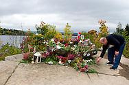 Vandaag mocht de pers voor het eerst weer op het eiland Utoya in Noorwegen bij Oslo, na de slachtpartij op 22-07-2011 waarbij 77 slachtoffers vielen. Een noorse bezoeker legt bloemen bij het herdenkingsmonument<br /> Foto: Geert van Erven