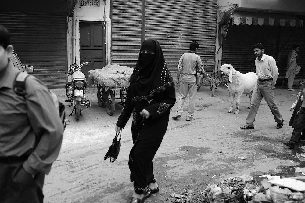 A woman in full black hijab walks in the streets of the Old City of Lahore. Pakistan, 2009