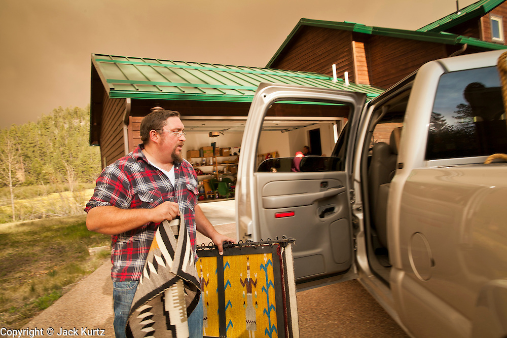 "04 JUNE 2011 - GREER, AZ: Robb Tyler (CQ 2 bb in Robb) packs up his home in Greer. Tyler said more than 5 generations of his family have been coming to Greer and this is the first time they've had to evacuate because of a fire. The fire grew to more than 140,000 acres early Saturday with zero containment. A ""Type I"" incident command team has taken command of the fire.  PHOTO BY JACK KURTZ"