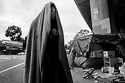 A woman who goes by the name T walks towards a friend's tent near Northgate Avenue and Sycamore Street on Thursday, May 25, 2017, in Oakland, Calif. She was temporarily removed from her tent around the corner as Oakland officials cleared the street for cleaning.