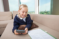 Little girl using calculator while studying on sofa