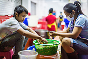 18 SEPTEMBER 2013 - BANGKOK, THAILAND:  Thai teenagers sort fruit in a market stall in the Chinatown section of Bangkok. Thailand in general, and Bangkok in particular, has a vibrant tradition of street food and eating on the run. In recent years, Bangkok's street food has become something of an international landmark and is being written about in glossy travel magazines and in the pages of the New York Times.     PHOTO BY JACK KURTZ