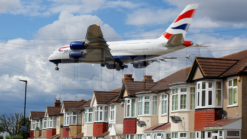 © Licensed to London News Pictures. 29/07/2015. Heathrow, UK. An aircraft coming in to land over houses at Heathrow airport. There has been a long running dispute over the expansion and extension of a third runway at the UK's largest airport. A recent report by the Airports Commission recommended that a third runway be built at Heathrow ahead of plans to build a new airport or expand Gatwick. Photo credit : Ian Wylie/LNP