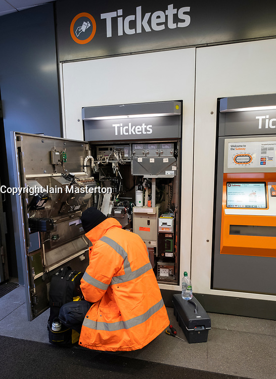 Technician repairing broken ticket machine inside station on the Glasgow Subway system in Glasgow, Scotland UK